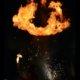 Feuerspuckflamme in Feuershow bei Wald leuchtet